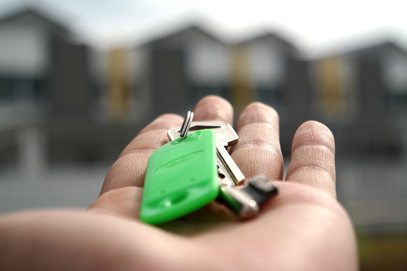 a person holding house keys on their hand showing that moving affects your mental health